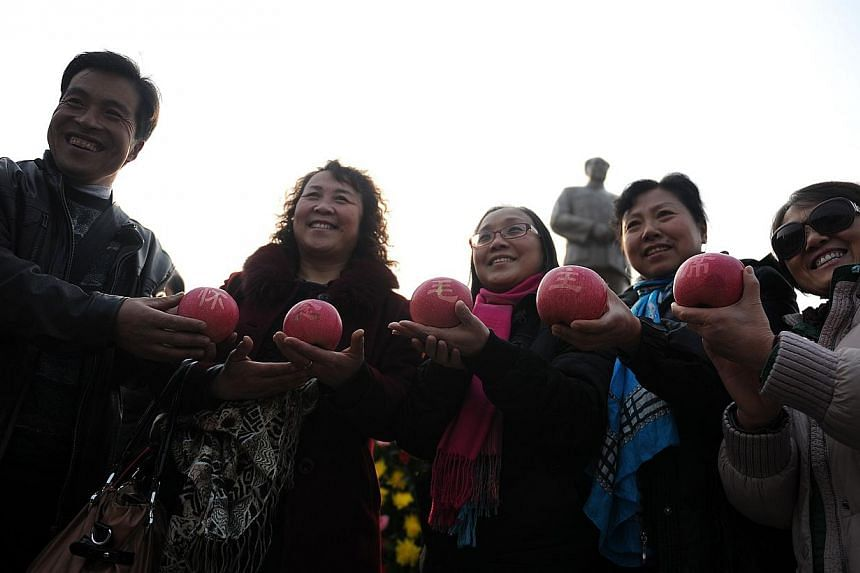 A group of people display apples with Chinese characters of Mao Zedong in front of a bronze statue of the former Chinese leader in Shaoshan, in China's central province of Hunan on Wednesday, Dec 25, 2013. -- PHOTO: AFP