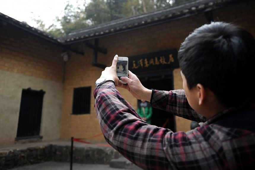 A man takes a photo at the former residence of former Chinese leader Mao Zedong in Shaoshan, in China's central province of Hunan on Wednesday, Dec 25, 2013. -- PHOTO: AFP