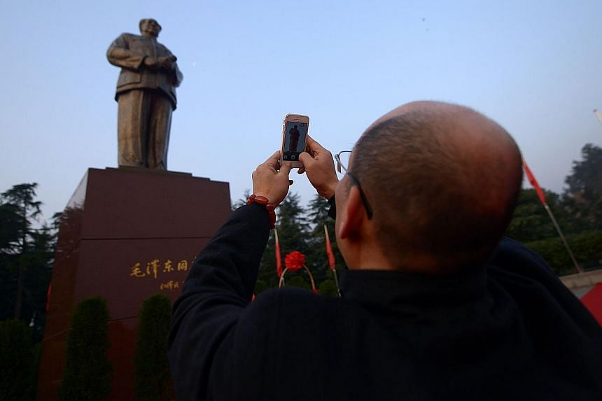 A man takes a photo in front of a bronze statue of former Chinese leader Mao Zedong at a square in Shaoshan, in China's central province of Hunan on Tuesday, Dec 24, 2013. -- PHOTO: AFP