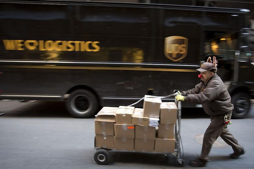 UPS delivery man Vinny Ambrosino prepares to deliver packages on Christmas Eve while wearing a Rudolf nose and antlers in New York, December 24, 2013. A high volume of holiday packages overwhelmed shipping and logistics company UPS, the company