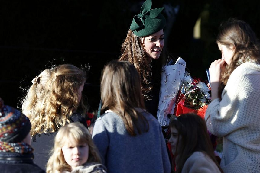 Britain's Catherine, Duchess of Cambridge, (second, right) receives flowers following a traditional Christmas Day Church Service at Sandringham in eastern England, on Dec 25, 2013 . Prince William said it had been a good first Christmas morning with