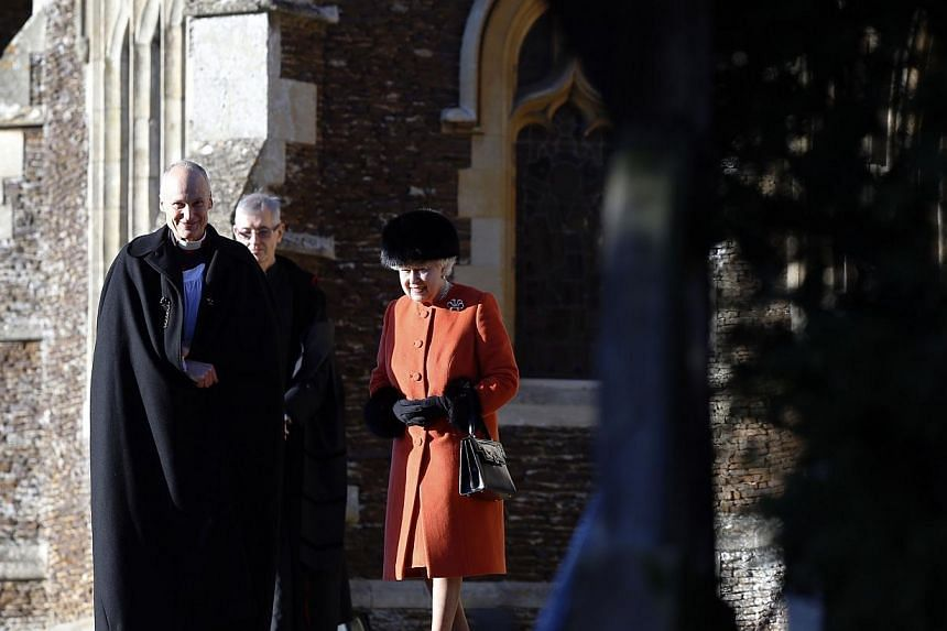 Britain's Queen Elizabeth II (right) is pictured as she leaves following a traditional Christmas Day Church Service at Sandringham in eastern England, on Dec25, 2013. While most people in Britain open their presents on Christmas Day, the royals follo