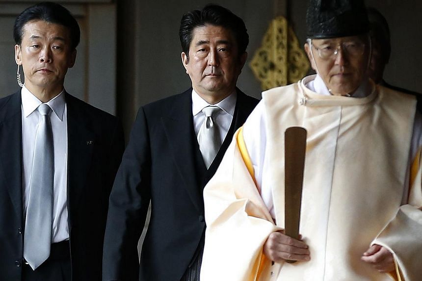 Japan's Prime Minister Shinzo Abe (centre) is led by a Shinto priest as he visits Yasukuni shrine in Tokyo on Dec 26, 2013. Mr Abe said on Thursday his visit to the controversial Yasukuni war shrine was a pledge that Japan would not go to war again a