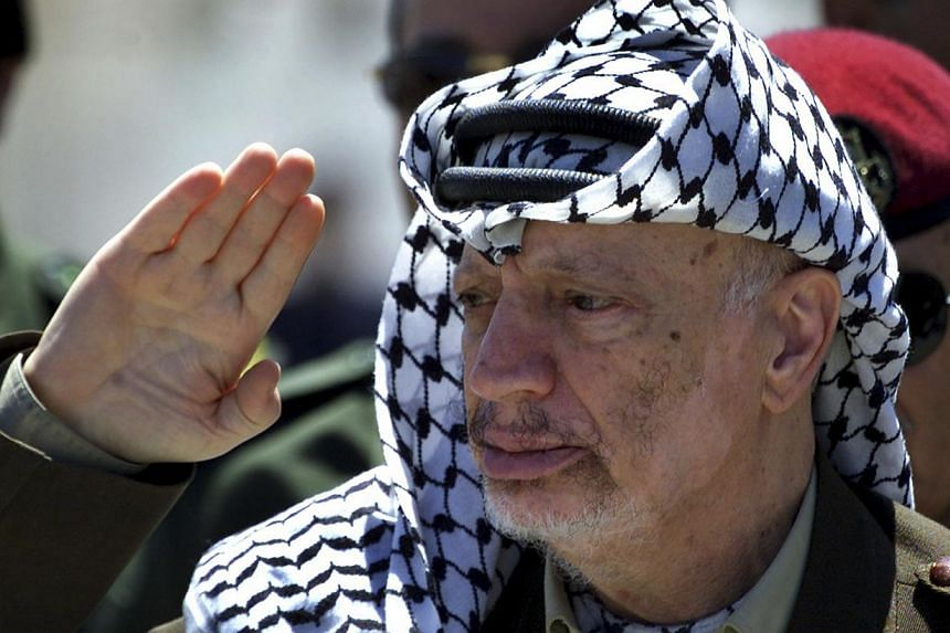 """Palestinian President Yasser Arafat reviews an honour guard on his arrival at the Gaza Strip on May 5, 2001.The Swiss expert who examined samples of Arafat's remains dismissed as a """"political declaration"""" a statement Thursday, Dec 26, 2013, by"""