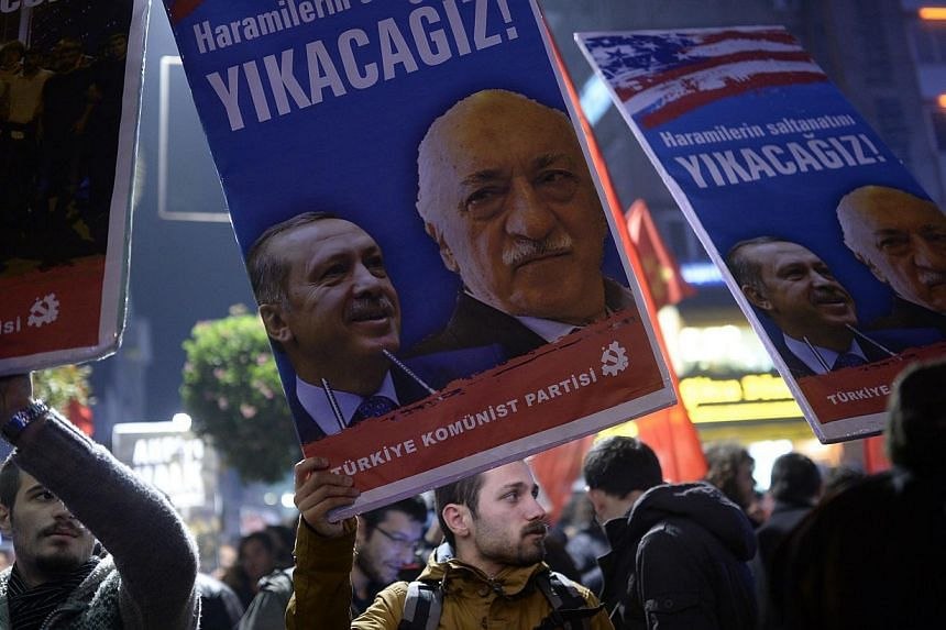 A Turkish protestor holds up a placard with pictures of Turkish Prime Minister Recep Tayyip Erdogan (left) and the United States-based Turkish cleric Fethullah Gulen during a demonstration against corruption in the Kadikoy district of Istanbul on Wed