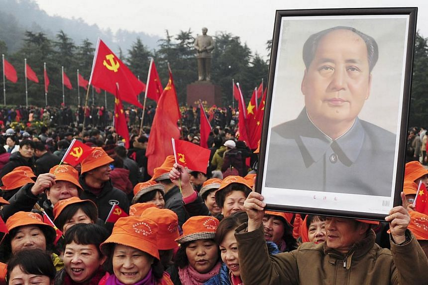 A man holds up a portrait of the late Chairman Mao Zedong as he and others gather in front of a giant statue of Mao on a square to celebrate the 120th birth anniversary of the former leader, in Shaoshan on Thursday, Dec 26, 2013.Communist China