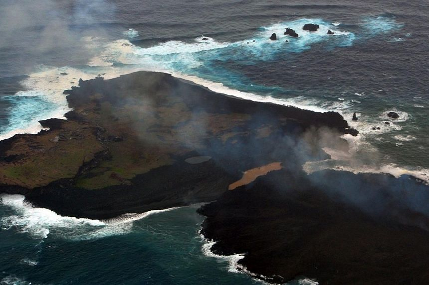 This handout picture taken by Japan Coast Guard on Dec 26, 2013, shows a newly created small islet (right) and Nishinoshima island (left), which are conjoined with erupting lava at the Ogasawara island chain, 1,000km south of Tokyo. A smouldering isl