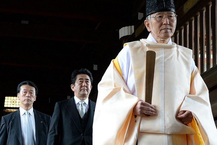 """A Shinto priest (right) leads Japanese Prime Minister Shinzo Abe (centre) as he visits the controversial Yasukuni war shrine in Tokyo, on Dec 26, 2013, in a move Beijing condemned as """"absolutely unacceptable"""".The United States is """"disappointed"""""""