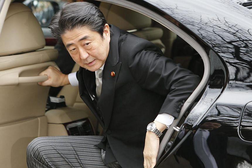 Japan's Prime Minister Shinzo Abe arriving at the controversial Yasukuni Shrine to pay tribute to the war dead, in Tokyo on Dec 26, 2013. Mr Abe prayed at Yasukuni - which enshrines a few million of Japan's war dead as well as 14 Class A war criminal