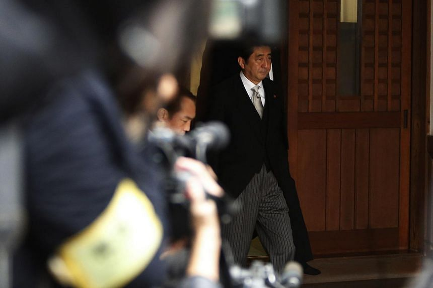 Japan's Prime Minister Shinzo Abe leaves the controversial Yasukuni Shrine after paying tribute to the war dead, near members of the media, in Tokyo on Dec 26, 2013. -- PHOTO: REUTERS