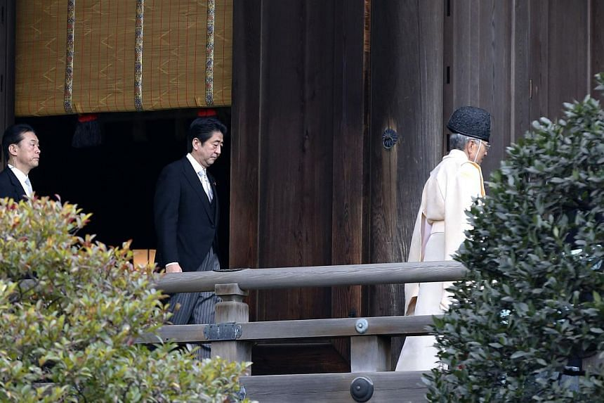 Japan's Prime Minister Shinzo Abe (2nd right) walks behind a Shinto priest as he visits Yasukuni shrine in Tokyo on Dec 26, 2013. -- PHOTO: REUTERS