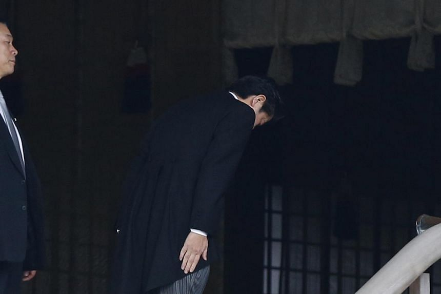Japan's Prime Minister Shinzo Abe (centre) bows as he visits Yasukuni shrine in Tokyo on Dec 26, 2013. -- PHOTO: REUTERS