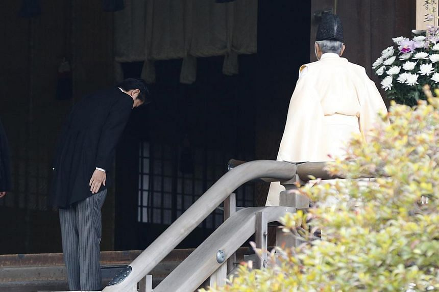 Japan's Prime Minister Shinzo Abe (centre) bows beside a Shinto priest as he visits Yasukuni shrine in Tokyo on Dec 26, 2013. -- PHOTO: REUTERS