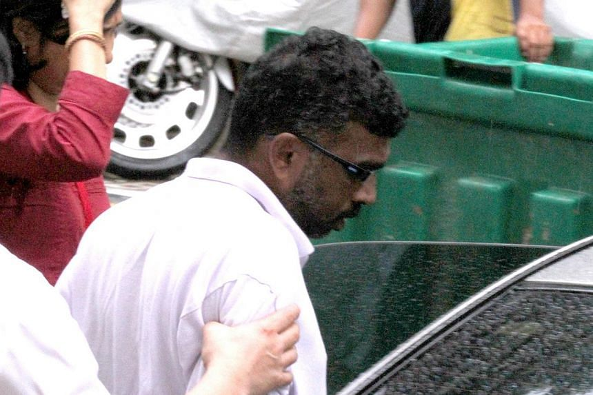 P. Mageswaran being led into the car after assisting with Police investigations. P. Mageswaran has been accused of murdering his godmother in Yishun was remanded for psychiatric assessment on Thursday. -- ST FILE PHOTO:  LATASHNI