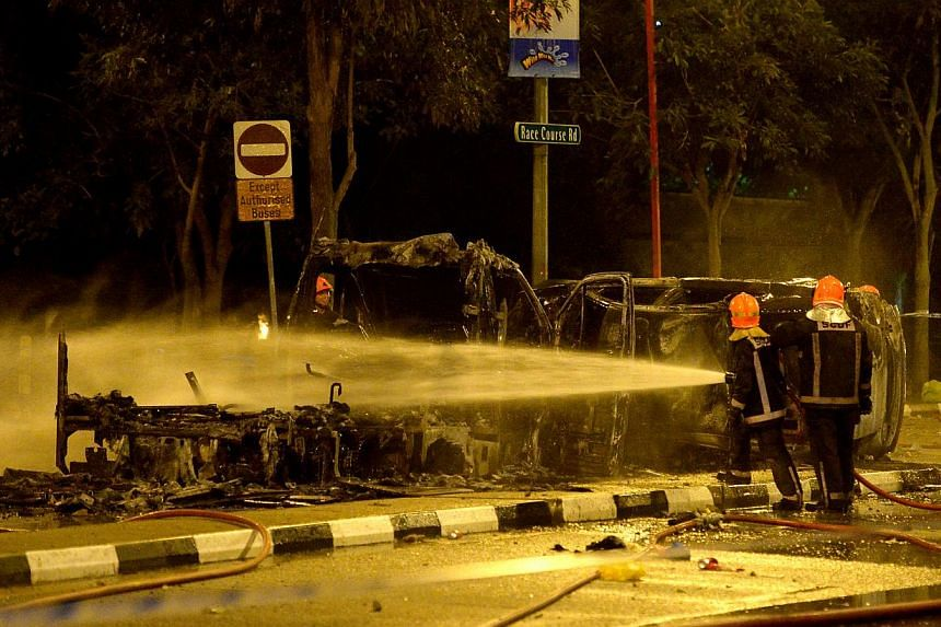 Firefighters (above) putting out the flames of a burning vehicle during the riot. -- ST PHOTO: JAMIE KOH