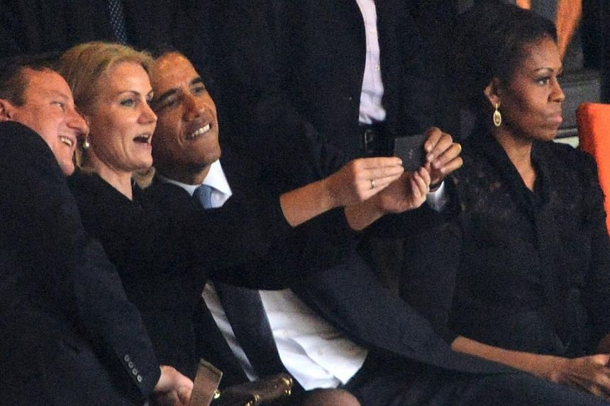 US President Barack Obama (right) and British Prime Minister David Cameron pose for a selfie picture with Denmark's Prime Minister Helle Thorning Schmidt (centre) next to US First Lady Michelle Obama (right) during the memorial service of South Afric