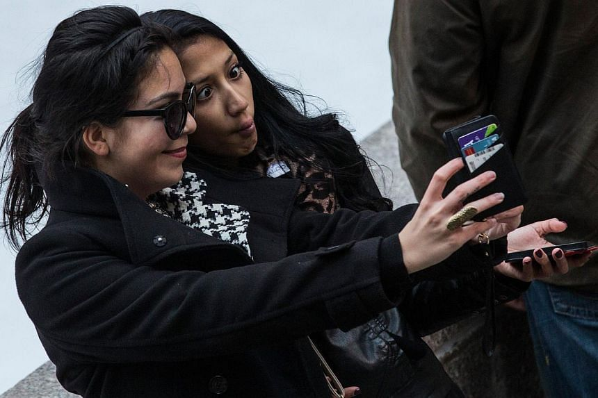 """Two women take a """"selfie"""" outside Rockefeller Center on Nov 19, 2013 in New York City. Self-portraiture has been around for centuries, but the global proliferation of smartphones with built-in digital cameras -- plus the ability to share photos insta"""