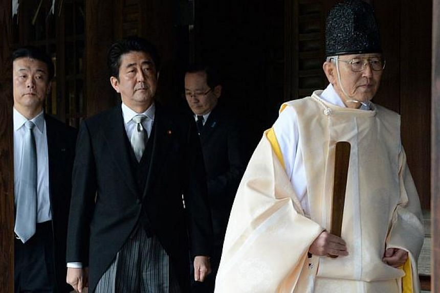"""A Shinto priest (right) leading Japanese Prime Minister Shinzo Abe (centre) as he visits the controversial Yasukuni war shrine in Tokyo on Dec 26, 2013. China must take """"excessive"""" counter-measures after Mr Abe's controversial war shrine visit, state"""
