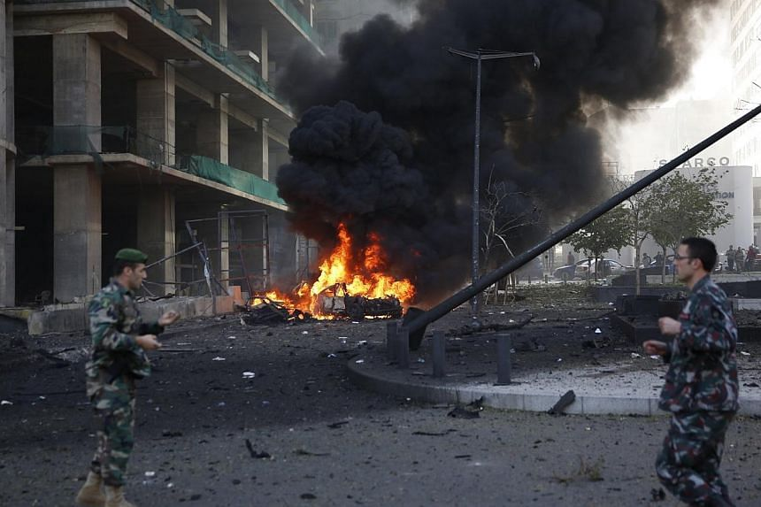 Lebanese army personnel run at the site of an explosion in Beirut's downtown area Dec 27, 2013. The explosion rocked the Lebanese capital on Friday, causing an unknown number of casualties. The blast was heard across the city and a plume of black smo