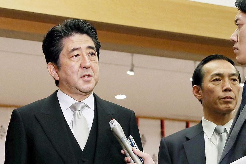 Japanese Prime Minister Shinzo Abe (centre) speaks to reporters as he visits and offers prayer at the controversial Yasukuni shrine at the shrine in Tokyo on Dec 26, 2013.Japanese media have strongly condemned Prime Minister Shinzo Abe's visit