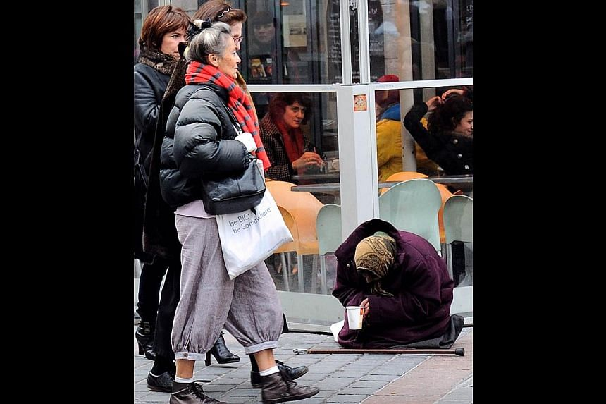 A woman begging in France. With the euro zone on the road to recovery, moderate growth can be expected. -- PHOTO: AGENCE FRANCE-PRESSE