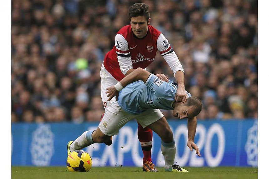 Manchester City's Pablo Zabaleta (right) is challenged by Arsenal's Olivier Giroud during their English Premier League soccer match at the Etihad stadium in Manchester, northern England, on Dec 14, 2013. Zabaleta has warned his team-mates they can't