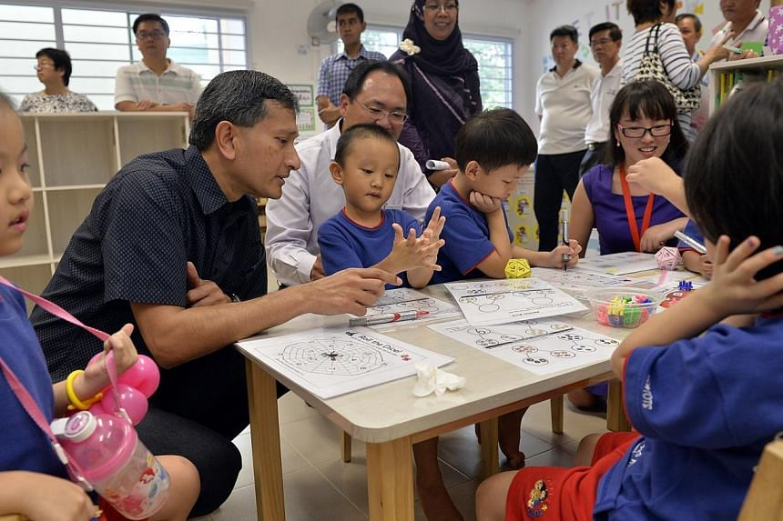 Mr Liang Eng Hwa(in white), MP for the Zhenghua district,and Dr Vivian Balakrishnan (second from left), Member of Parliament for Holland-Bukit Timah and Environment and Water Resources Minister,interact with some of the children dur