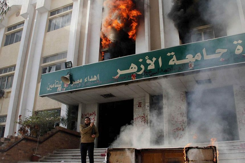 A man stands outside a faculty building at Cairo's Al-Azhar University after student supporters of the Muslim Brotherhood stormed it on Dec 28, 2013.A student was killed and 60 arrested as Egyptian police entered a Cairo university on Sat