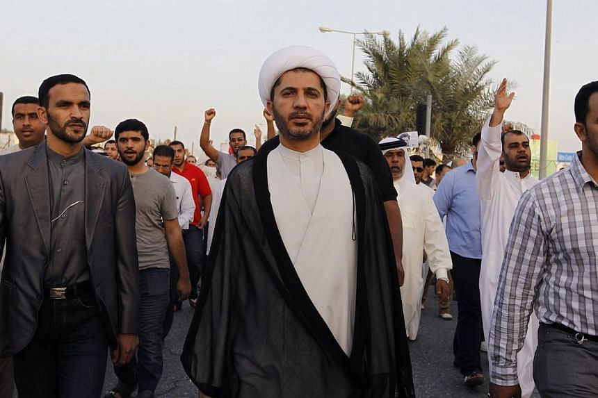 General Secretary of Al-Wefaq, Ali Salman (centre), walks as protesters behind him shout anti-government slogans during a rally organized by Bahrain's main opposition party Al Wefaq in Budaiya, west of Manama, on Dec 13, 2013. Bahrain police have arr