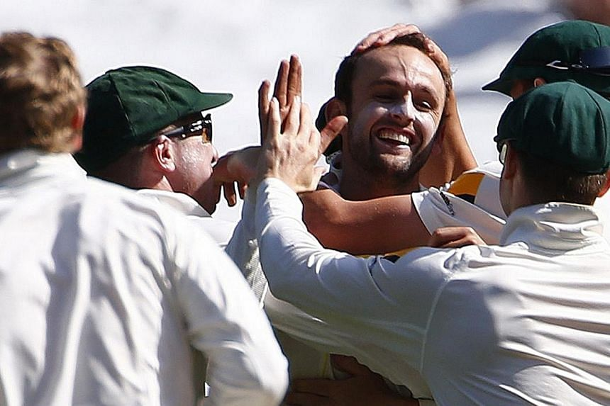 Australia's Nathan Lyon celebrates with team mates after taking five wickets in an inning during the third day of the fourth Ashes cricket test against England at the Melbourne cricket ground, on Dec 28, 2013. In an astonishing third day of the