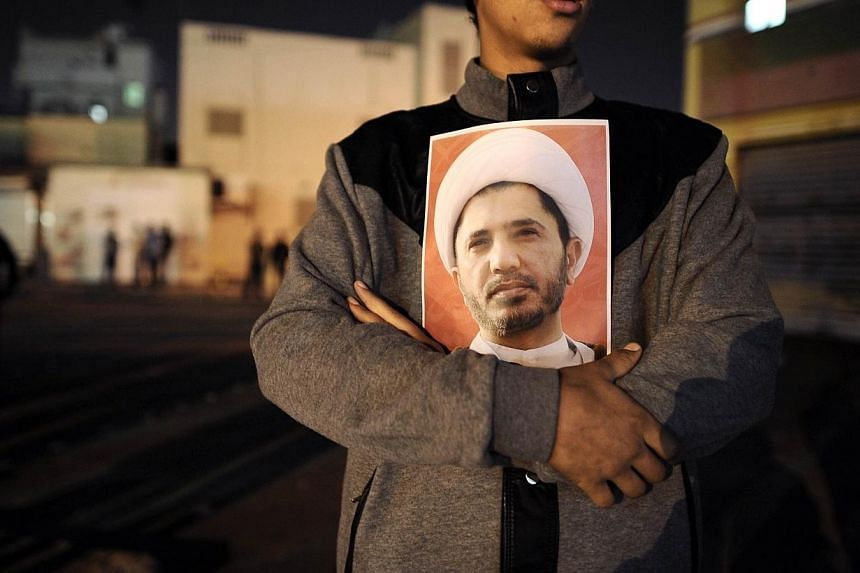 A man holds a portrait of Ali Salman late on Dec 28, 2013, at Bilad al-Qadeem, a suburb of Manama, as police use tear gas during a protest after police arrested Salman, head of the main Shi'ite opposition bloc Al-Wefaq that has spearheaded protests a