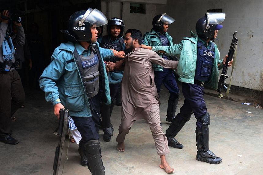 Bangladeshi police detain a suspected activist of Hizb-ut-Tahrir, a banned Islamist militant organisation in Dhaka on Dec 27, 2013, as Hizb-ut Tahrir supporters attempted a demonstration march following Friday prayers.Bangladesh police fired wa