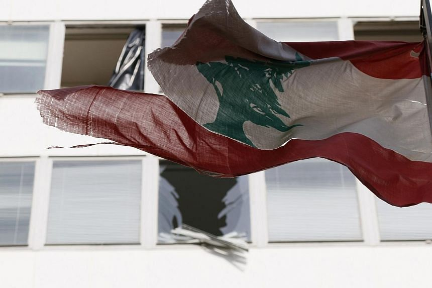 Lebanon's flag flies in front of damaged windows at the Starco building in front of the site of a bomb blast, which killed Lebanon's former Finance Minister Mohamad Chatah, in downtown Beirut Dec 28, 2013.  Heavy security measures were in p