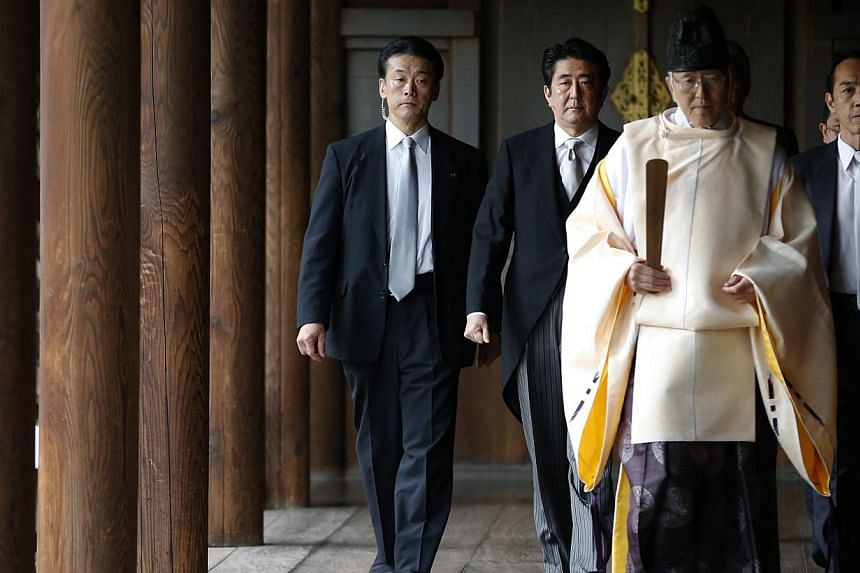 Japan's Prime Minister, Shinzo Abe (second from left), is led by a Shinto priest as he visits Yasukuni shrine in Tokyo, on Dec 26, 2013. -- PHOTO: REUTERS