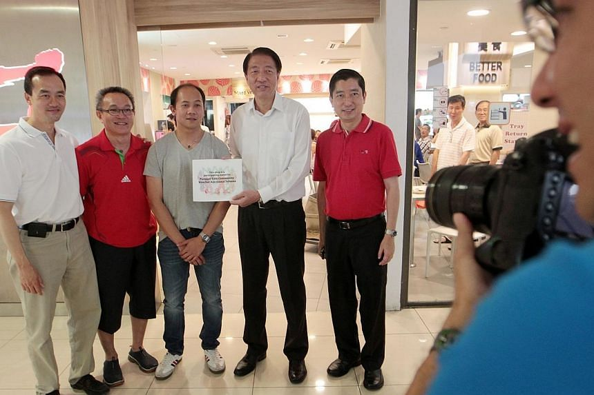 Deputy Prime Minister Teo Chee Hean (fourth from left) and Dr Koh Poh Koon (extreme left) pose for a group photograph with Koufu staff with the decal that indicates that the shop is one of the 17 participating shops under the Punggol East Community V