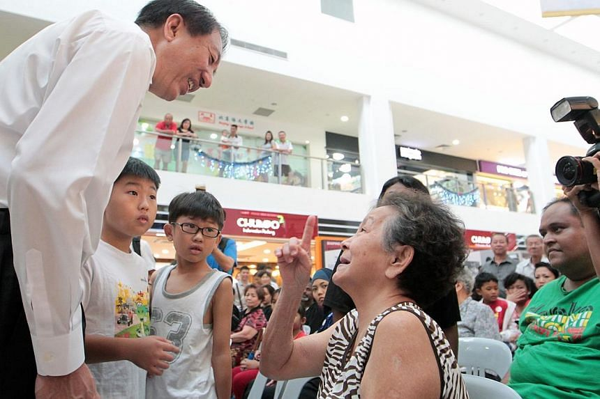 Deputy Prime Minister Teo Chee Hean gives out community vouchers to needy residents in North East CDC at Rivervale Plaza on Dec 29, 2013. -- ST PHOTO: NEO XIAOBIN