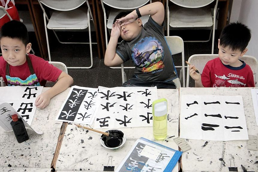 (Above, from left) Joshua Poh, Ajay Bhattarai and Kody Ronald Kwok attending a youth calligraphy class at the Chinese Calligraphy Society of Singapore. (Below) Six-year-old Chloe Chia (in green) joining her classmates in cleaning the ink off their br