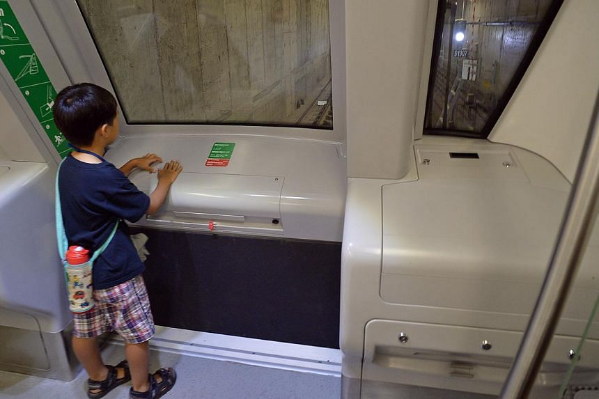 A child resting his hands on the cover of the detrainment switch on a Downtown Line train yesterday. The switch, which would lower a ramp for emergency evacuation, could have been activated by the movement of the cover, causing power to be cut as a s