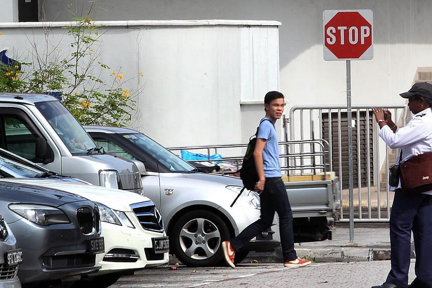 A URA carpark warden snapping a photo of a car before issuing a summons. The handheld device used to issue summonses can now take photos too. -- ST PHOTO: LAU FOOK KONG
