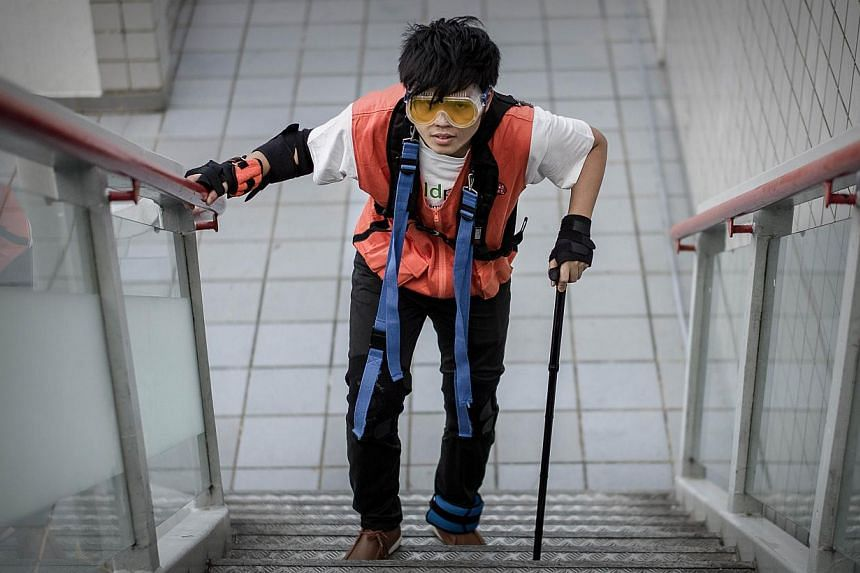 This picture taken on Oct 25, 2013, shows a man from Hong Kong social awareness program Eldpathy wearing an artificial impediment suit that helps limit a person's vision and motion to recreate what elderly people deal with on a daily basis, in Hong K