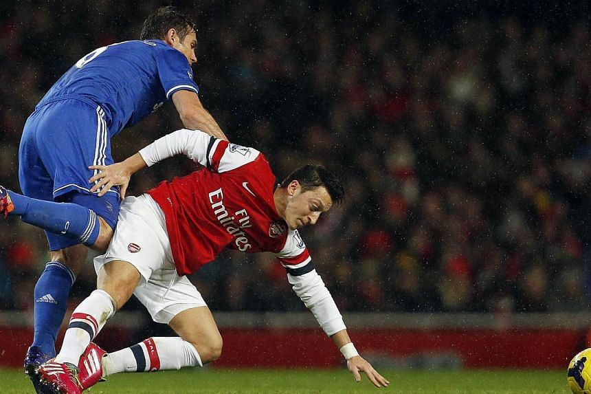 Arsenal's German midfielder Mesut Oezil (right) vies with Chelsea's English midfielder Frank Lampard during the English Premier League football match between Arsenal and Chelsea at the Emirates Stadium on Dec 23, 2013. Oezil will be out for up t