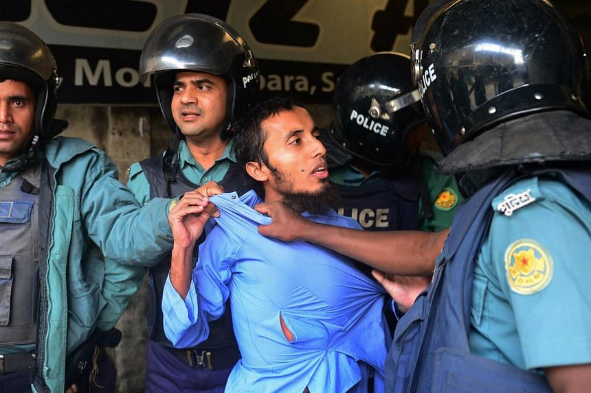 Bangladeshi police detain a suspected activist of Hizb-ut-Tahrir, a banned Islamist militant organisation in Dhaka on Dec 27, 2013, as Hizb-ut Tahrir supporters attempted a demonstration march following Friday prayers. Bangladesh opposition protester