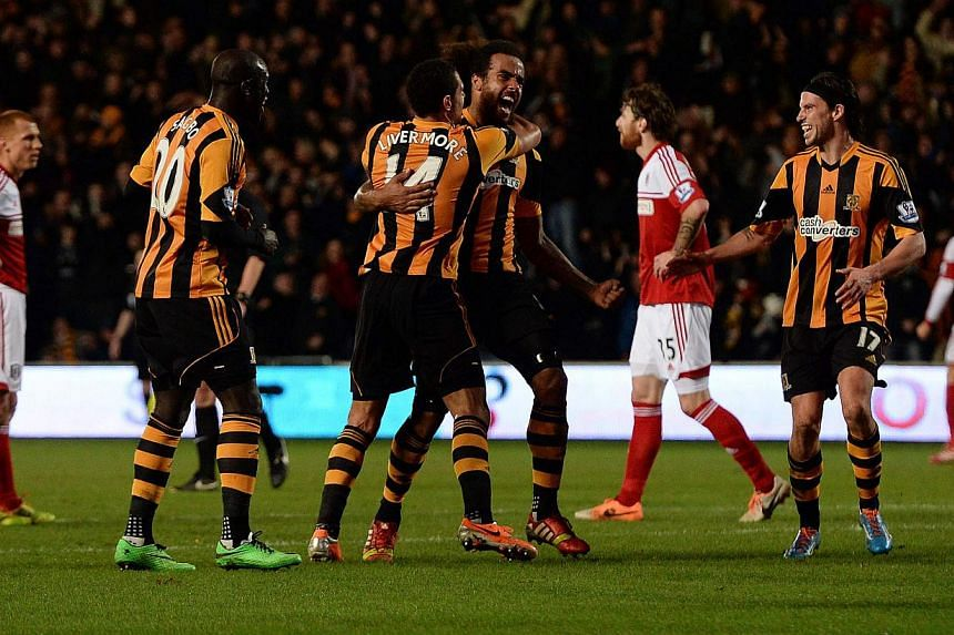 Hull City's Tom Huddlestone (centre) celebrates scoring with Jake Livermore against Fulham during their English Premier League soccer match at The KC Stadium in Hull, northern England, on Dec 28, 2013. Hull ended a disappointing run of form in emphat