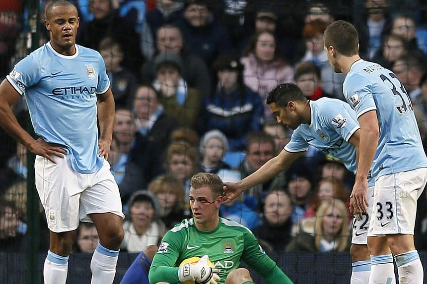 Manchester City goalkeper Joe Hart (centre) waits to be treated for an eye injury after clashing with Crystal Palace's Cameron Jerome during their English Premier League soccer match at the Etihad stadium in Manchester, northern England on Dec 28, 20