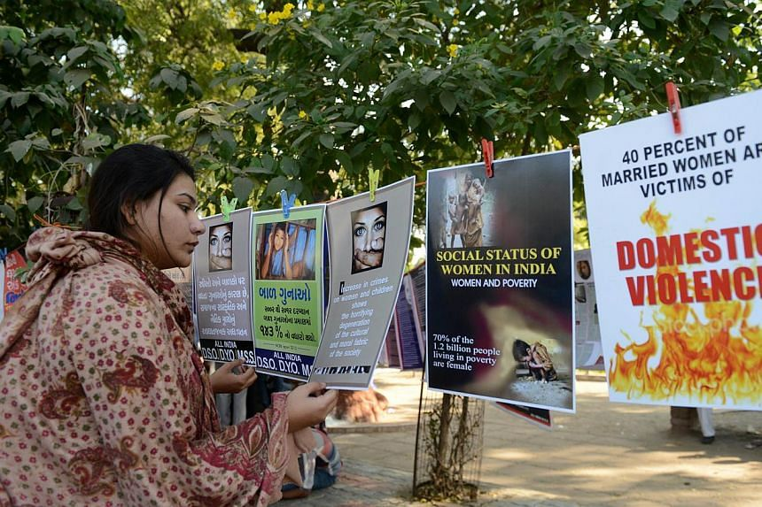 An Indian woman looks at posters exhibited during a program commemorating the December 2012 fatal gang-rape of a 23-year old New Delhi student, in Ahmedabad on Dec 16, 2013. -- FILE PHOTO: AFP