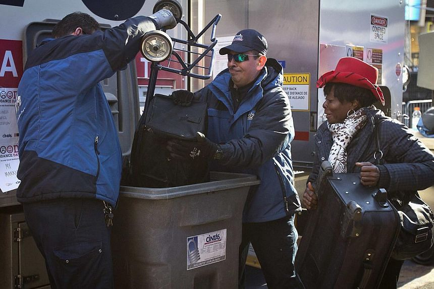 """Workers dump a woman's cart full of paper into a shredder during """"Good Riddance Day"""" in Times Square in New York on Dec 28, 2013. -- PHOTO: REUTERS"""