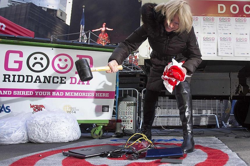 "Ms Jody Watkins smashes old computers as part of ""Good Riddance Day"" in Times Square in New York, on Dec 28, 2013. -- PHOTO: REUTERS"