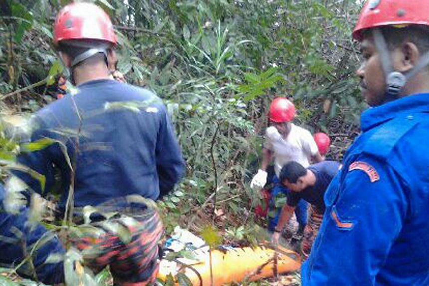 Rescuers with the body of Mr Lee Jun Jie, a National University of Singapore (NUS) student who died while on a camping trip in Kelantan on Saturday, Dec 28, 2013.National University of Singapore (NUS) undergraduate Lee Jun Jie drowned aft