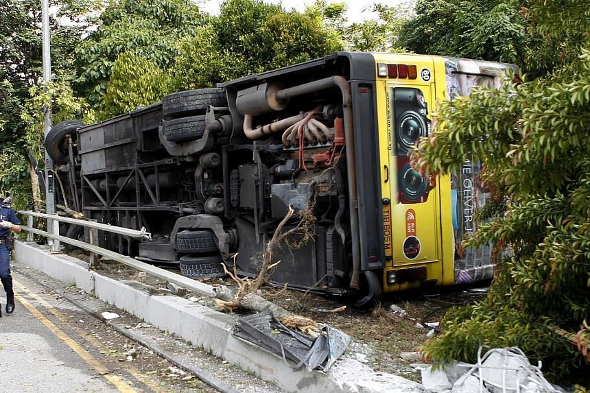 The scene of a road accident involving SMRT bus service 700A which overturned on July 21, 2013.An SMRT bus driver was charged on Monday with causing the death of a passenger and injuring another in an accident which occurred in July this
