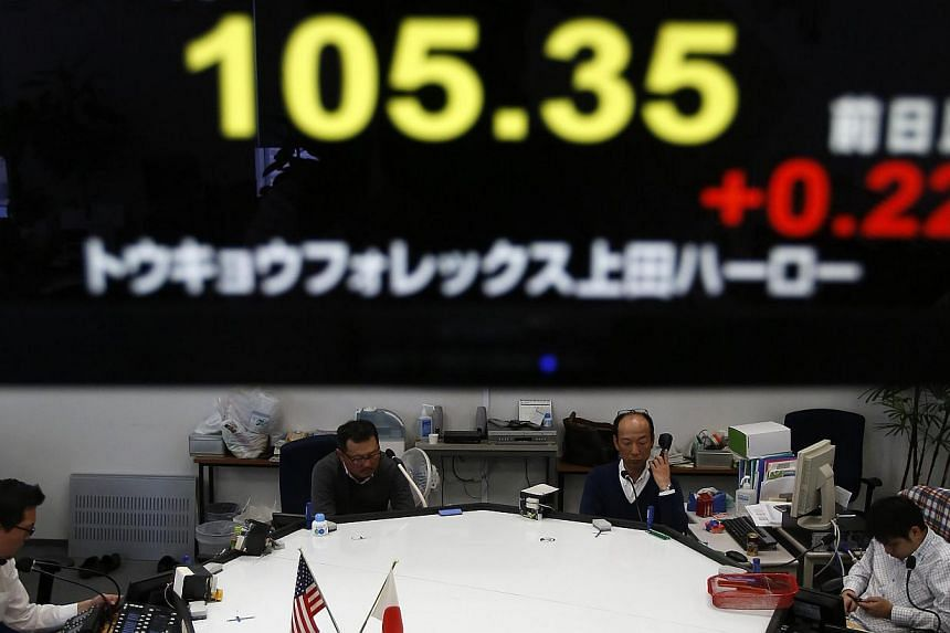 Employees of a foreign exchange company work under a screen displaying the Japanese yen's exchange rate against the US dollar in a dealing room in Tokyo on Monday, Dec 30, 2013. Moves by Japan's central bank to stimulate the economy have sent th